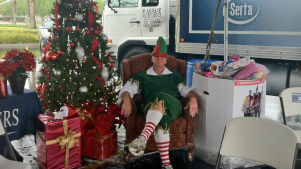 Garth the Elf rests his feet and eyes at the Stuff-A-Bus toy drive at Mathis Brothers Furniture in Ontario on Friday, Nov. 30, 2012.