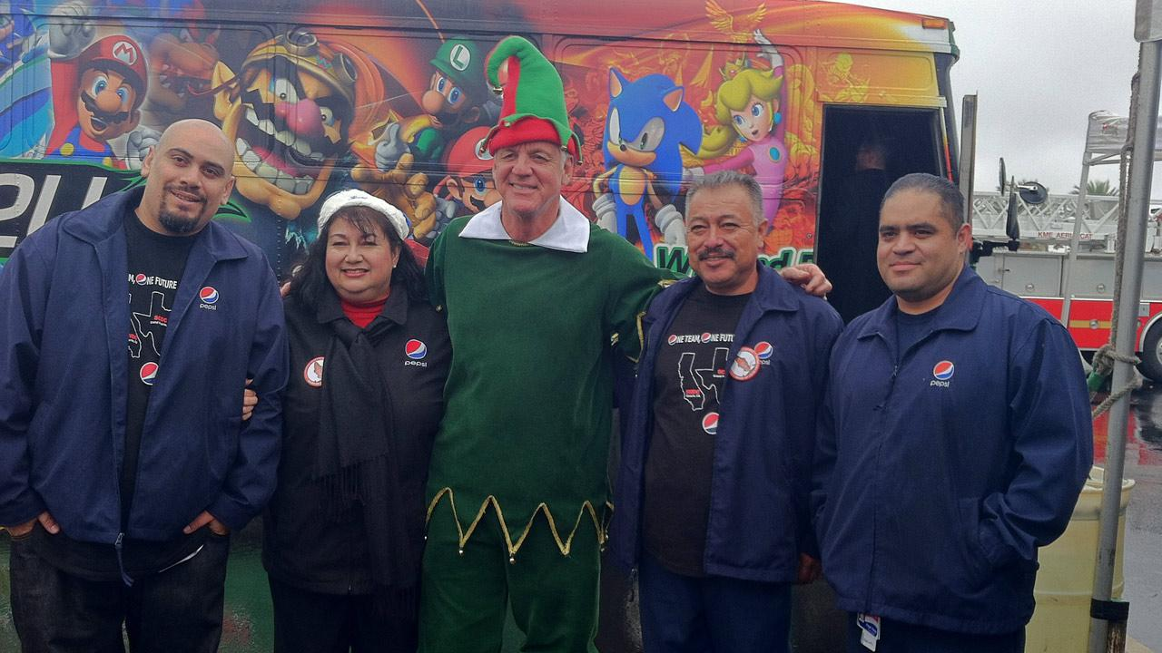 Garth the Elf poses with Pepsi employees at the Stuff-A-Bus toy drive at Mathis Brothers Furniture in Ontario on Friday, Nov. 30, 2012.