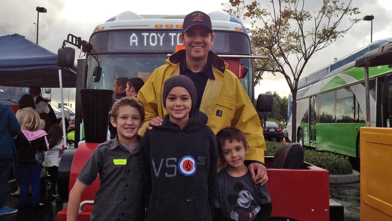 Ontario firefighter Victor Lopez and his sons at the Stuff-A-Bus toy drive at Mathis Brothers Furniture in Ontario on Friday, Nov. 30, 2012.