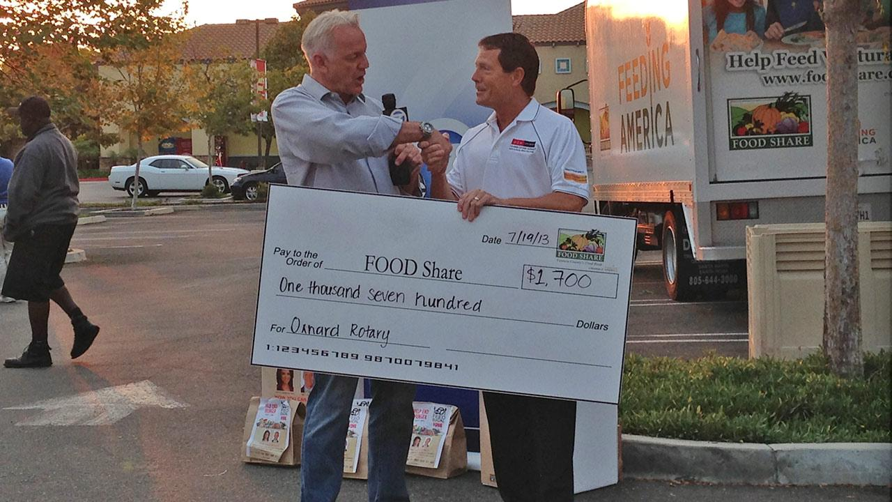 ABC7 Weathercaster Garth Kemp poses with Tim Lauerbach with the Oxnard Rotary Club, who donated $1,700 to support the Feed SoCal initiative in Thousand Oaks on Friday, July 19, 2013.