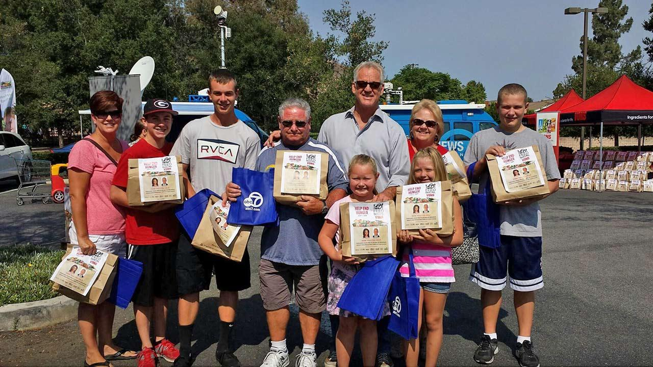 ABC7 Weathercaster Garth Kemp poses with the Hodgins family at the Feed SoCal initiative in Thousand Oaks on Friday, July 19, 2013.