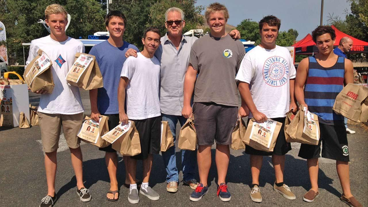 ABC7 Weathercaster Garth Kemp poses with members from a local water polo team, who donated food at the Feed SoCal event in Thousand Oaks on Friday, July 19, 2013.