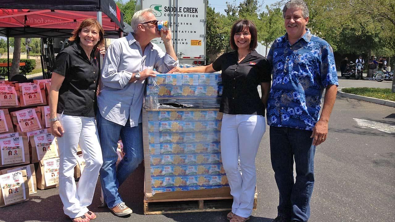 ABC7 Weathercaster Garth Kemp poses with representatives from Dole, who donated canned goods at the Feed SoCal event in Thousand Oaks on Friday, July 19, 2013.