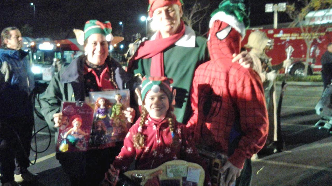The Herrmann Family of Fontana poses with ABC7s resident elf Garth Kemp at the Stuff-a-Bus event in Ontario Friday, Dec. 6, 2013.