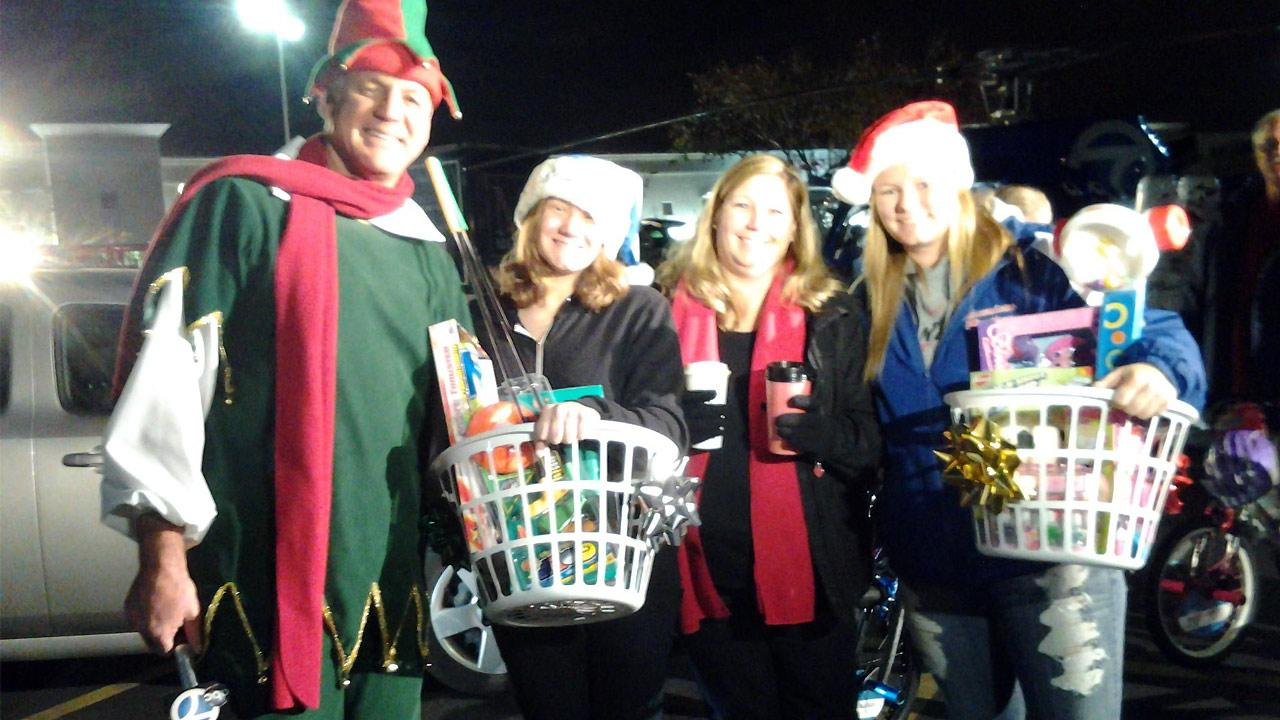 The Stigler Family of Rancho Cucamonga poses with ABC7s resident elf Garth Kemp at the Stuff-a-Bus event in Ontario Friday, Dec. 6, 2013.