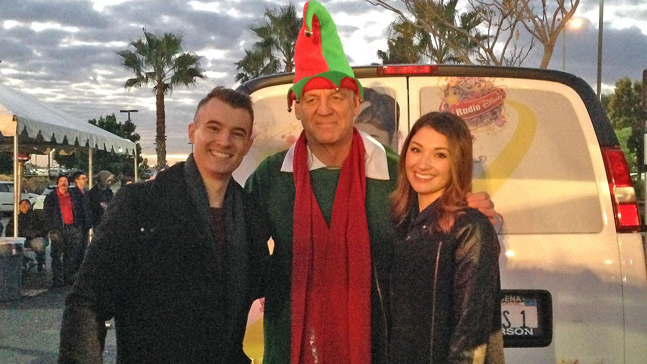 Morgan and Maddy from Radio Disney pose with ABC7s resident elf Garth Kemp at the Stuff-a-Bus event in Ontario Friday, Dec. 6, 2013.