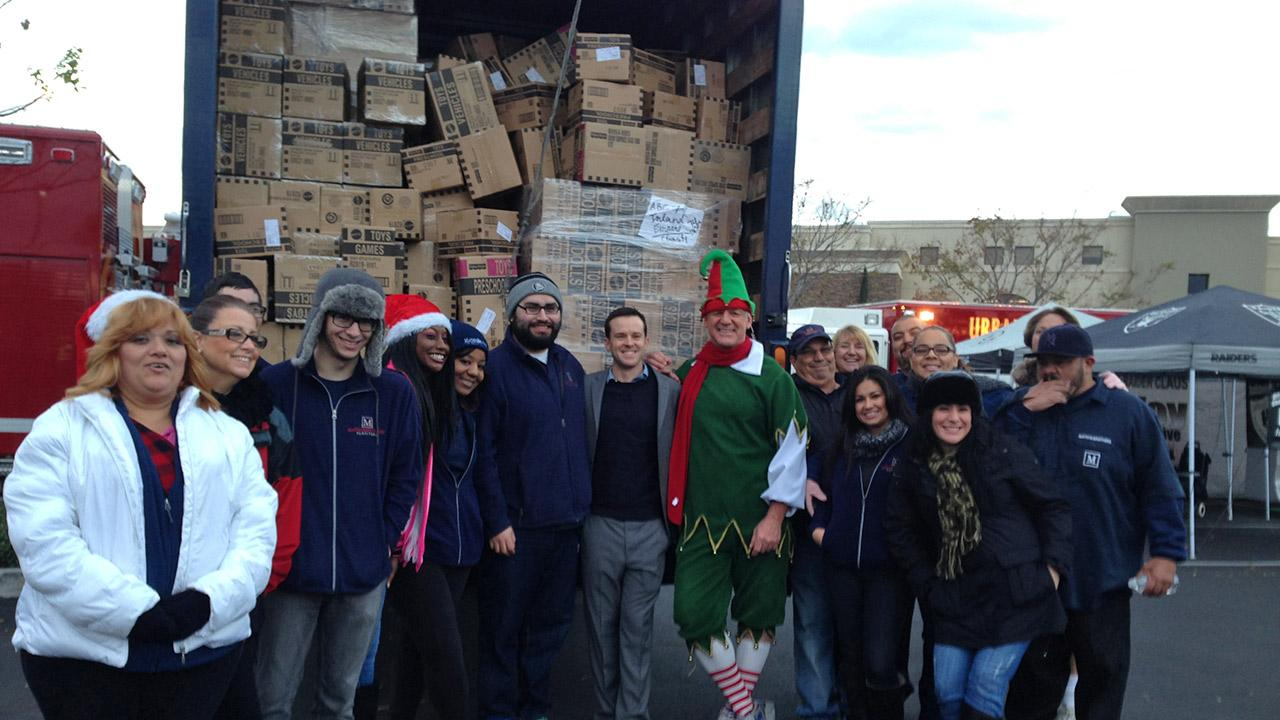 Members of the Mathis Brothers team pose with ABC7s resident elf Garth Kemp at the Stuff-a-Bus event in Ontario Friday, Dec. 6, 2013.