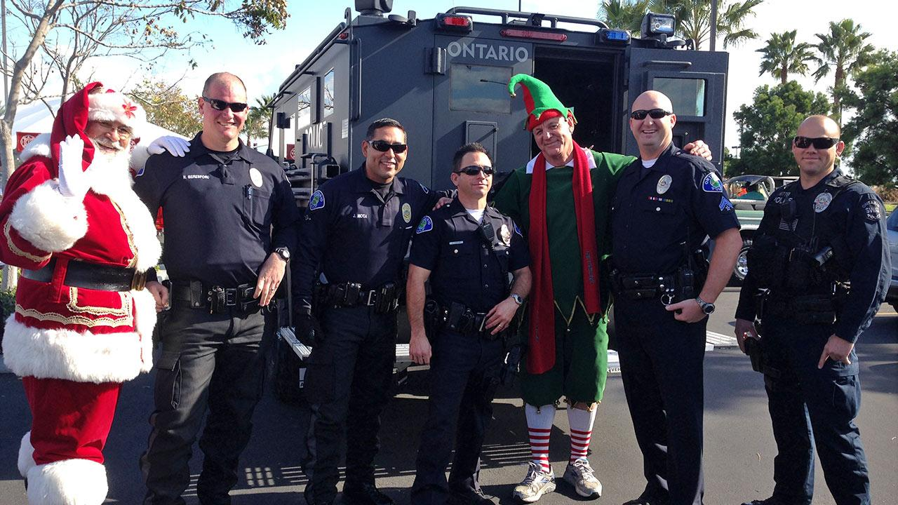 Garth the Elf poses with members of the Ontario Police Department at our Stuff-A-Bus event at Mathis Brothers in Ontario on Friday, Dec. 6, 2013.