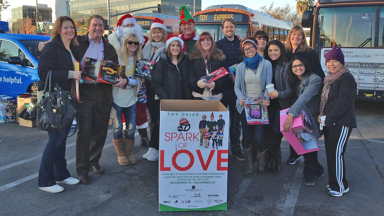 Garth the elf poses with a group of people who donated to the Stuff-a-Bus event in Canoga Park on Friday, Dec. 13, 2013.