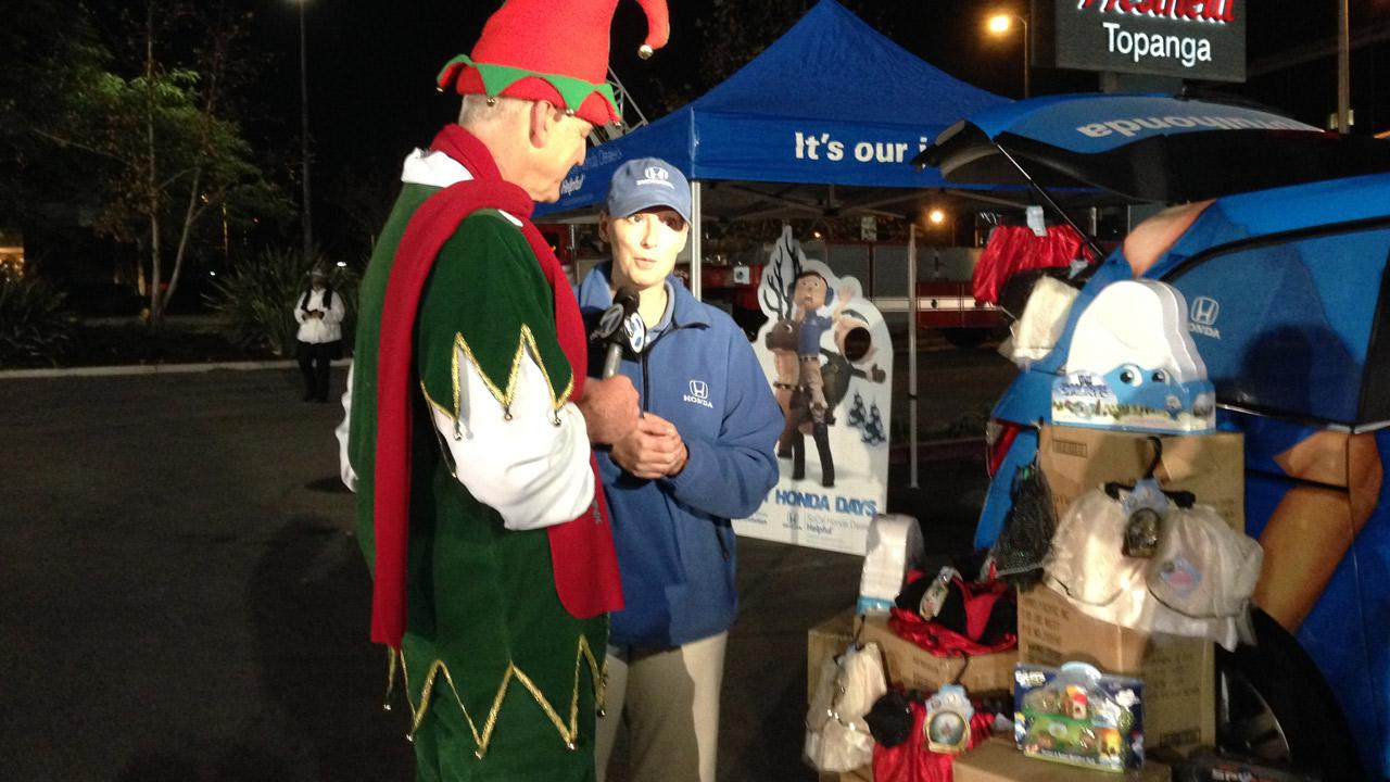 A Helpful Honda team member speaks to Garth the elf about their donation to the Stuff-a-Bus event in Canoga Park on Friday, Dec. 13, 2013.