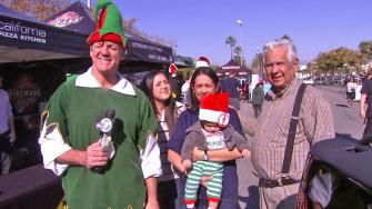 Garth the Elf poses with a family at the Spark of Love Toy Drive in Canoga Park on Friday, Dec. 13, 2013.