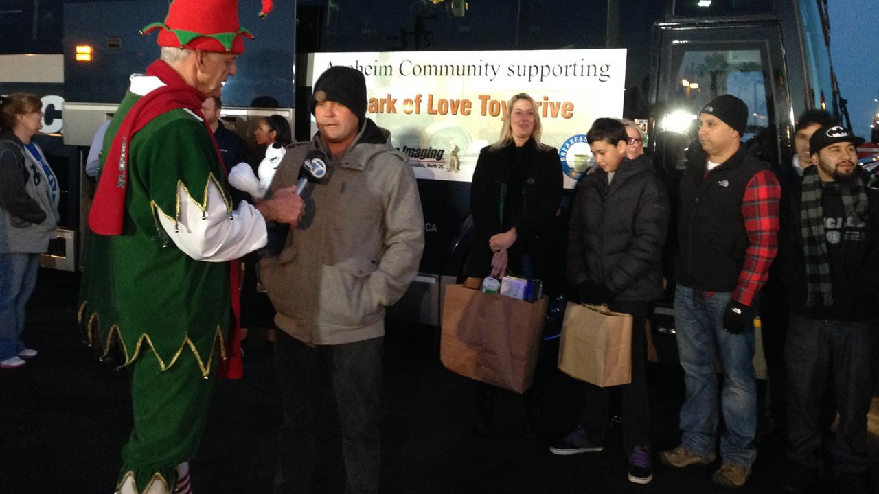 A representative of Lux Bus speak to Garth the Elf after donating toys to the Stuff-a-Bus event at the Honda Center in Anaheim on Friday, Dec. 20. 2013.