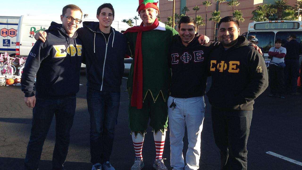 Members of Sigma Phi Epsilon at UC Riverside pose with Garth the Elf at the Stuff-a-Bus event at the Honda Center in Anaheim on Friday, Dec. 20. 2013.