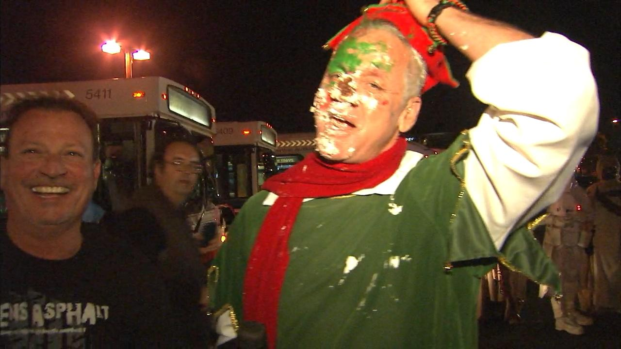 Garth the Elf celebrates with some cake after stuffing 16 buses at the Honda Center in Anaheim on Friday, Dec. 20, 2013.