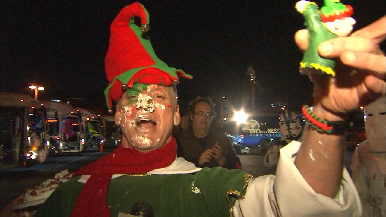 Garth the Elf celebrates with some cake after stuffing 16 buses at the Honda Center in Anaheim with some cake on Friday, Dec. 20, 2013.