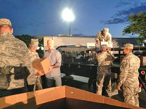 ABC7 Weathercaster Garth Kemp and members of the California Air National Guard unload a car full of food donations at the Feed SoCal event in Ontario on Friday, July 26, 2013. <span class=meta>(KABC Photo)</span>