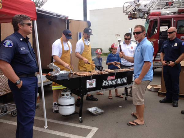 Fire volunteers grill food at the Feed SoCal event in Costa Mesa on Friday, July 26, 2013. <span class=meta>(KABC Photo)</span>
