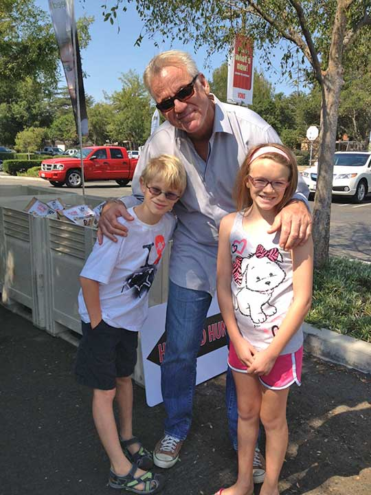 ABC7 Weathercaster Garth Kemp poses with Megan and Mathew from Thousand Oaks, who donated food to the Feed SoCal event in Thousand Oaks on Friday, July 19, 2013. <span class=meta>(KABC Photo)</span>