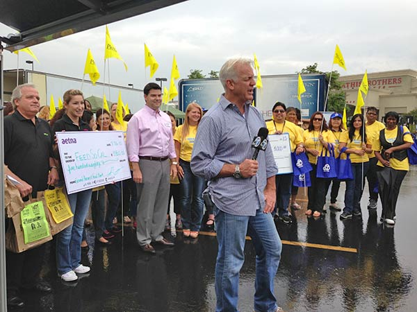 ABC7 Weathercaster Garth Kemp stands in front of PrimeCare and Aetna employees, who donated generously to the Feed SoCal food drive in Ontario on Friday, July 26, 2013. <span class=meta>(KABC Photo)</span>