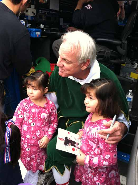 "<div class=""meta ""><span class=""caption-text "">Garth the Elf poses with two girls at the 'Spark of Love Toy Drive' at Los Cerritos Center on Friday, Nov. 18, 2011. (KABC Photo)</span></div>"