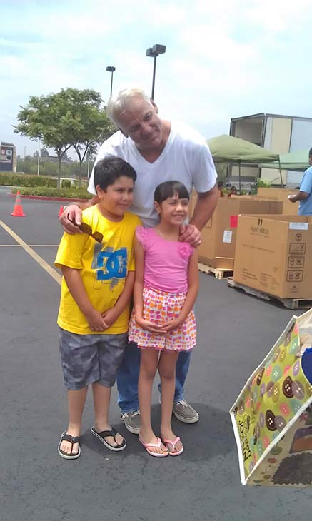 Elijah and Hannah from San Dimas pose for a photo with ABC7 Weathercaster Garth Kemp at the Feed SoCal food drive in Ontario on Friday, July 26, 2013. <span class=meta>(KABC Photo)</span>