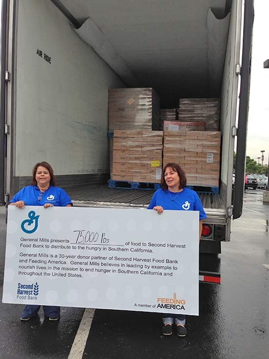 General Mills representatives hold up a sign indicating their donation of 75,000 pounds of food at the Feed SoCal food drive in Ontario on Friday, July 26, 2013. <span class=meta>(KABC Photo)</span>