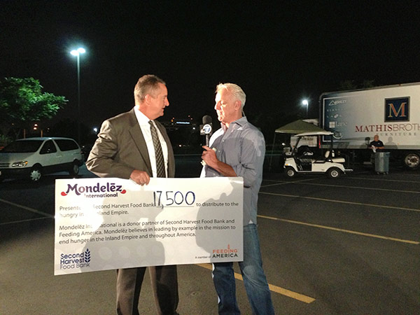 "<div class=""meta ""><span class=""caption-text "">ABC7 Weathercaster Garth Kemp speaks to a Mondelez International representative, who donated a check for $17,500 to the Feed SoCal event in Ontario on Friday, July 26, 2013. (KABC Photo)</span></div>"