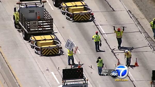 Workers removed cones and traffic signs blocking lanes on the 405 Freeway as they prepared to reopen Sunday, July 17, 2011.