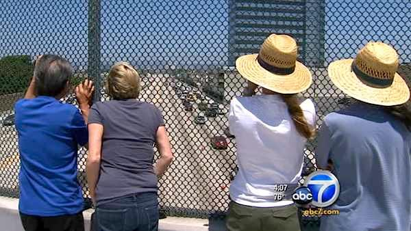 Curious spectators watch traffic flowing on Interstate 405 after it reopened Sunday, July 17, 2011.