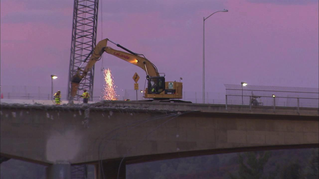 Sparks are seen as crews work on demolishing the north side of the Mulholland Drive Bridge on Saturday, Sept. 29, 2012.