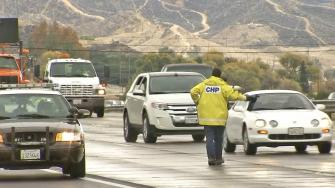 A California Highway Patrol officer directs traffic along the 5 Freeway near the Grapevine on Saturday, Dec. 7, 2013.