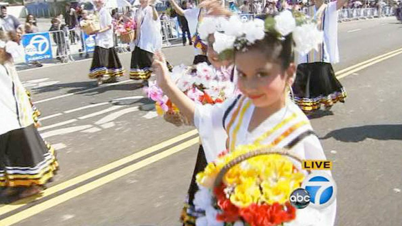 A little girl dressed in a traditional costume smiles while participating in the annual Mexican Independence Day Parade in East Los Angeles on Sunday, Sept. 9, 2012.