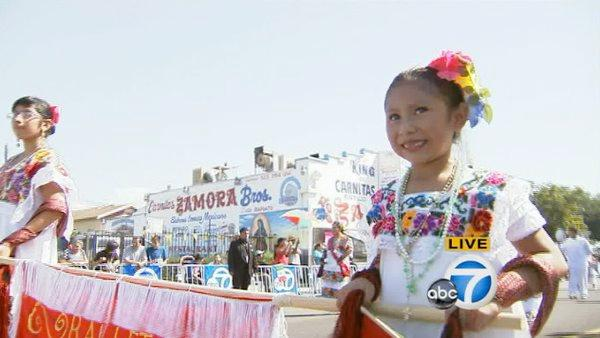 A young girl wearing a traditional costume smiles as she participates in the Mexican Independence Day Parade on Sunday, Sept. 9, 2012.