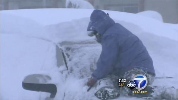 Driver attempts to dig car out of snow