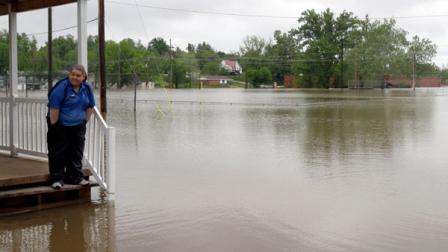 Erica Cross stands on a friends porch surrounded by floodwater Tuesday, April 26, 2011, in Poplar Bluff, Mo.