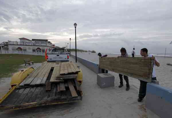 Town workers, from right, Jose Pineda, Travis Thompson, and Cager Jones, install barriers on the boardwalk as Hurricane Earl heads toward the eastern coast in Atlantic Beach, N.C., Thursday, Sept. 2, 2010.  <span class=meta>(AP Photo&#47; Chuck Burton)</span>