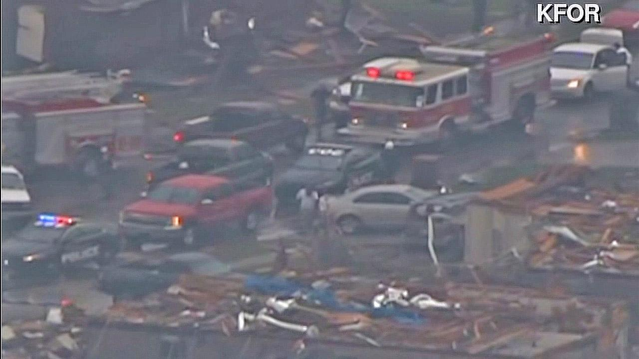 Authorities are seen after a tornado struck a neighborhood in Moore, Okla., on Monday, May 20, 2013.