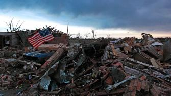 An American flag blows in the wind at sunrise atop the rubble of a destroyed home a day after a tornado moved through Moore, Okla., Tuesday, May 21, 2013.