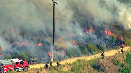 Firefighters scrambled to contain a brush fire in the Brea area on Thursday, July 7, 2011.