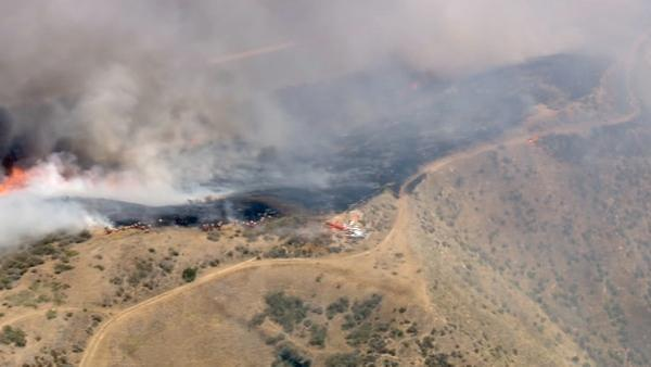 Smoke rises above the hills of Castaic, where a brush fire broke out along Interstate 5 on Friday, June 8, 2012. F