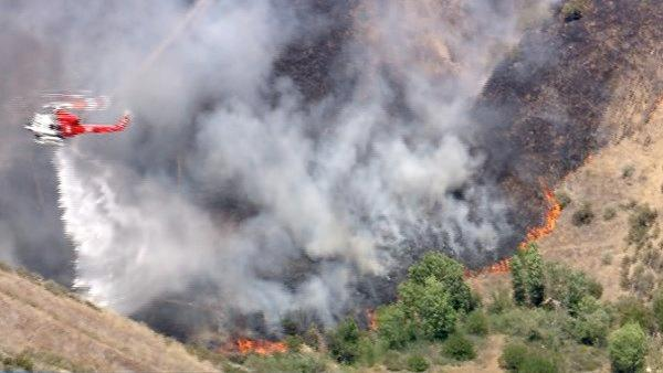 A helicopter makes a water drop on a brush fire burning in the Castaic hills on Friday, June 8, 2012. Fanned by winds, the blaze