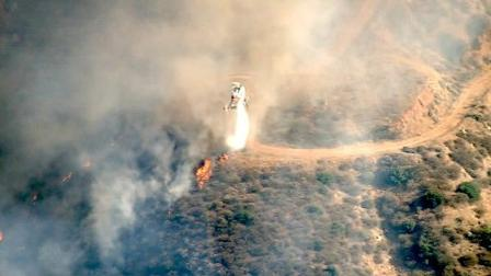 A helicopter is seen dousing part of a major brush fire in Beaumont on Saturday, June 16, 2012.