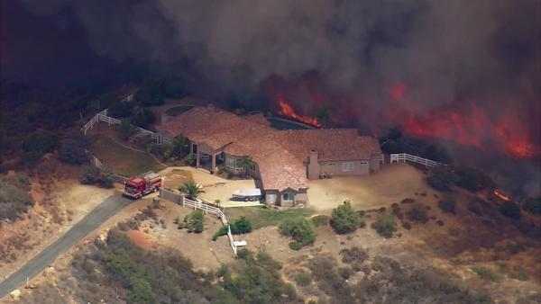 A brush fire threatened a residence in Murrieta on Wednesday, Aug. 1, 2012.