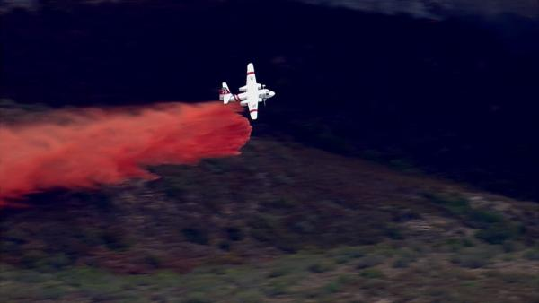 A plane drops flame retardant on