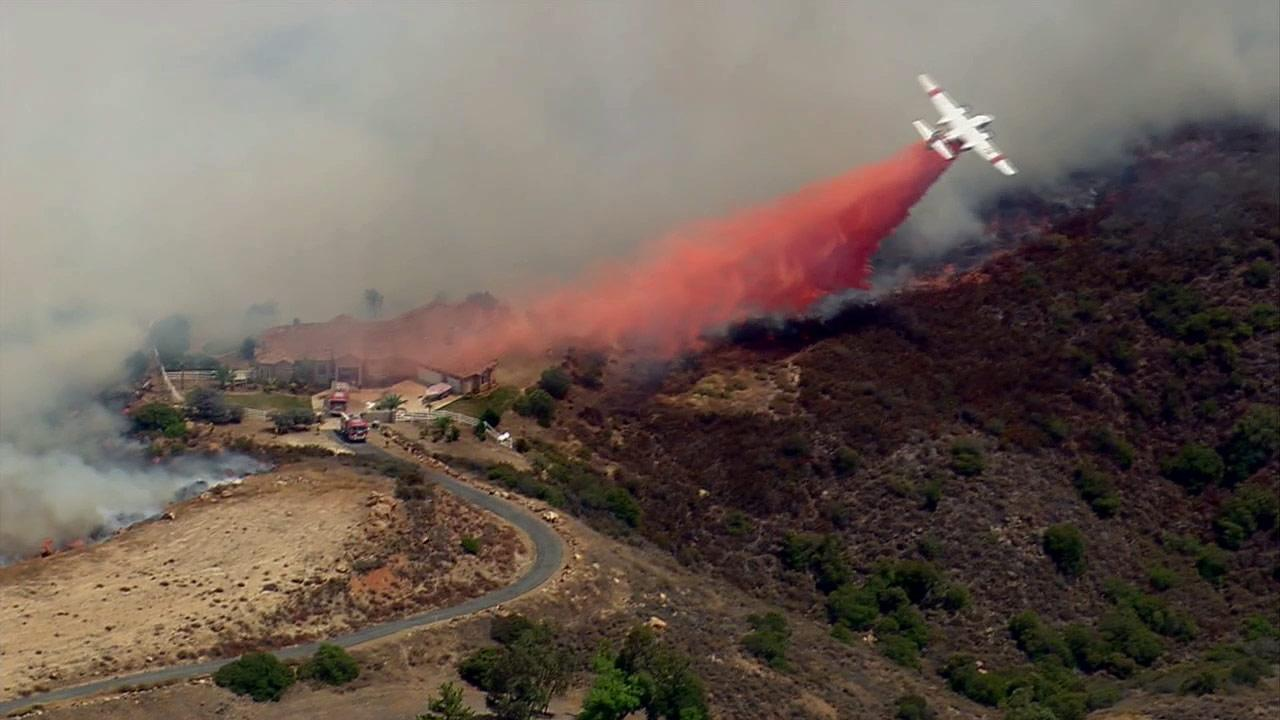 A plane drops fire retardant over fire threatening a residence in Murrieta on Wednesday, Aug. 1, 2012.