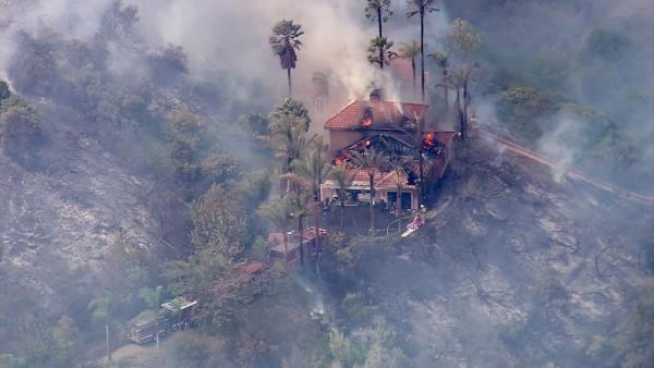 A brush fire burned at least one residence in Murrieta on Wednesday, Aug. 1, 2012.