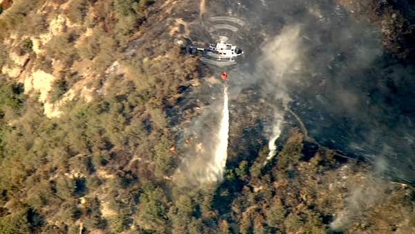 A helicopter makes a water drop over a wildfire burning in the San Gabriel Mountains above Glendora on Sunday, Sept. 2, 2012. About 1,500 recreationists and residents were evacuated in that part of the wilderness.