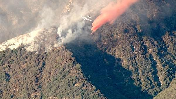 A small plane makes a drop over a wildfire in the San Gabriel Mountains above Glendora on Sunday, Sept. 2, 2012. About 1,500 recreationists and residents were evacuated in that part of the wilderness.