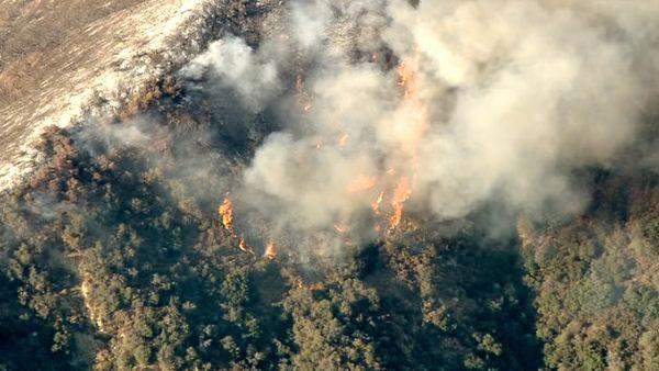 Smoke rises above a wildfire burning in the San Gabriel Mountains above Glendora on Sunday