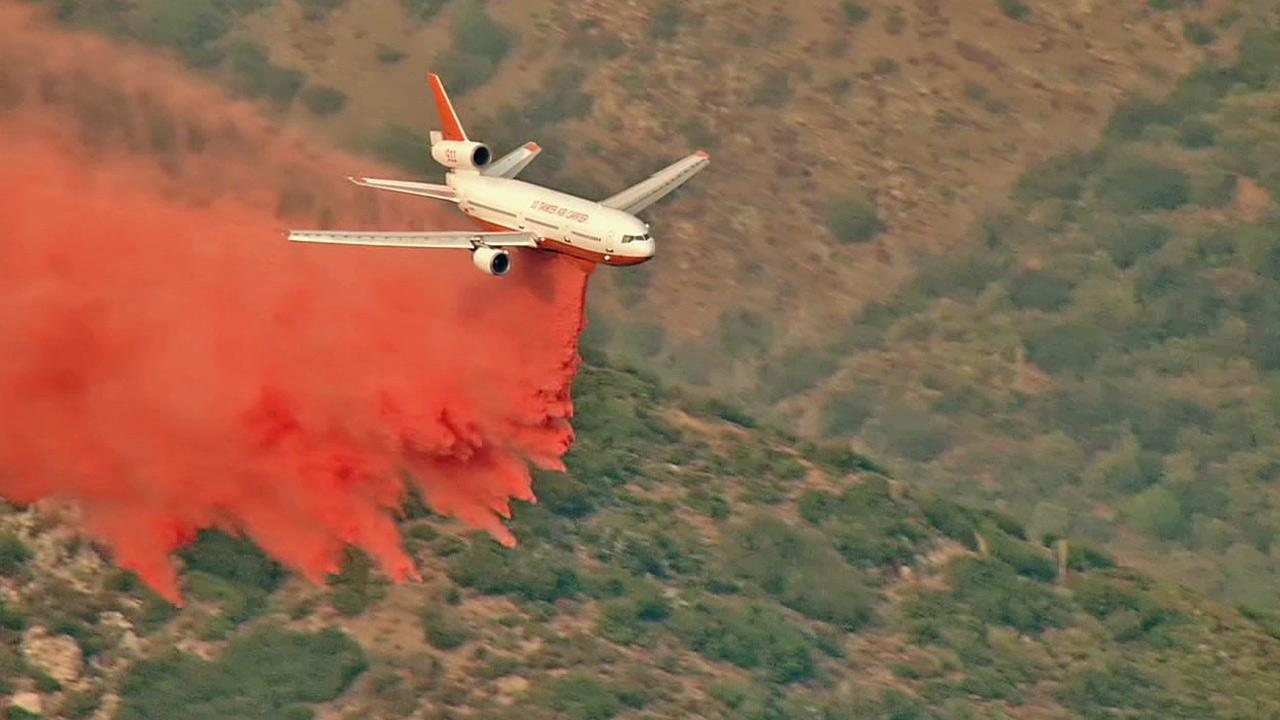 A plane drops fire retardant over the Williams Fire in the Angeles National Forest.